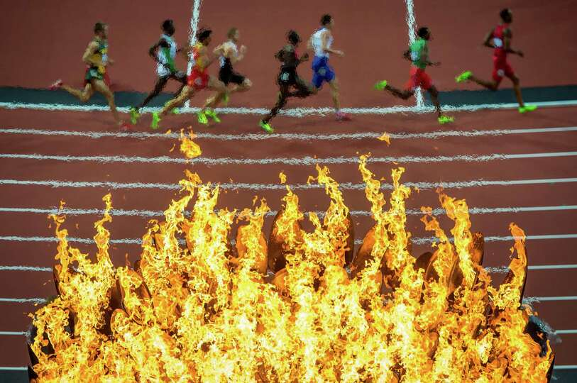 Runners pass beneath Olympic flame during the men's 800-meter semifinals at the 2012 London Olympics