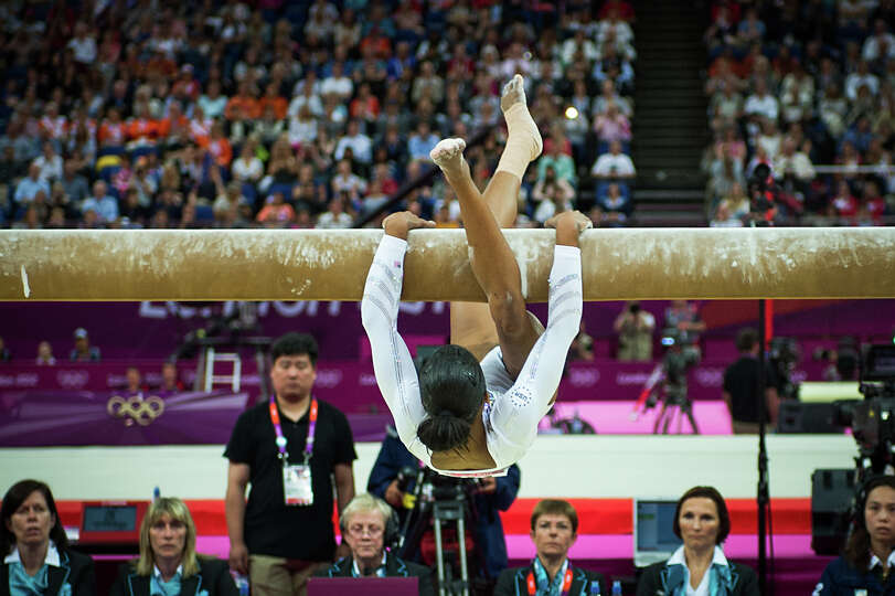 Gabrielle Douglas of the USA clings to the balance beam during the women's gymnastics apparatus fina