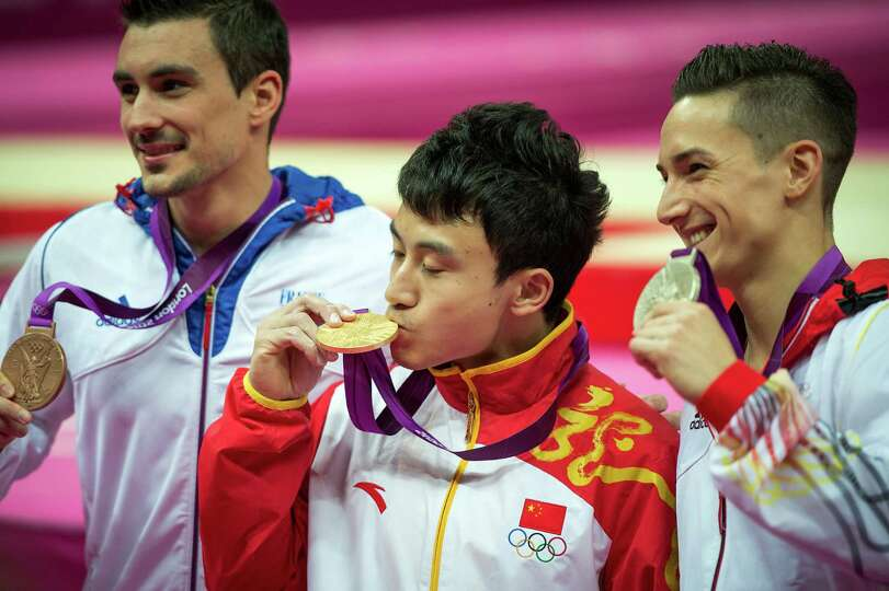 Feng Zhe of China, center, kisses his gold medal, as silver Marcel Nyugen of Germany, right, display