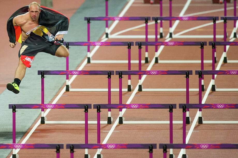 Robert Harting of Germany jumps hurdles as he takes a victory lap after winning the gold medal in the men's discus throw finals at the 2012 London Olympics on Tuesday, Aug. 7, 2012. Photo: Smiley N. Pool, Houston Chronicle / © 2012  Houston Chronicle