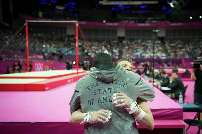 Jonathan Horton of the USA, facing, gets a hug from teammate Danell Leyva after competing in the men
