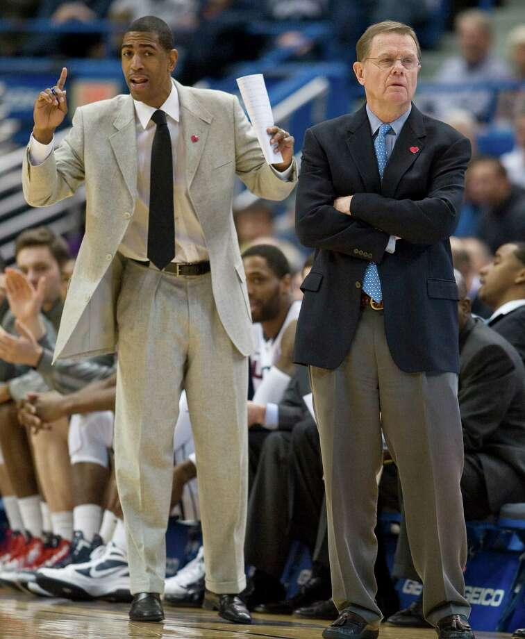 Associated head coach George Blaney, right, and assistant coach Kevin Ollie watch play during the first half of an NCAA college basketball game against Marquette in Hartford, Conn., Saturday, Feb. 18, 2012.  Marquette won 79-64. (AP Photo/Jessica Hill) Photo: Jessica Hill, Associated Press / AP2012