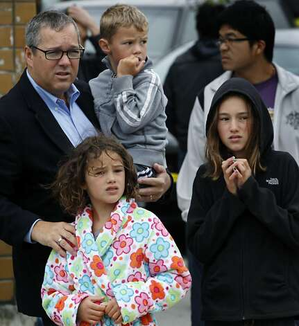 Left, Ken Piper, who lives on the street behind the three businesses destroyed by the blaze, watches firefighters mop up on Ocean Avenue, with son Cole and daughters Coco and Ella (right). Photo: Paul Chinn, The Chronicle