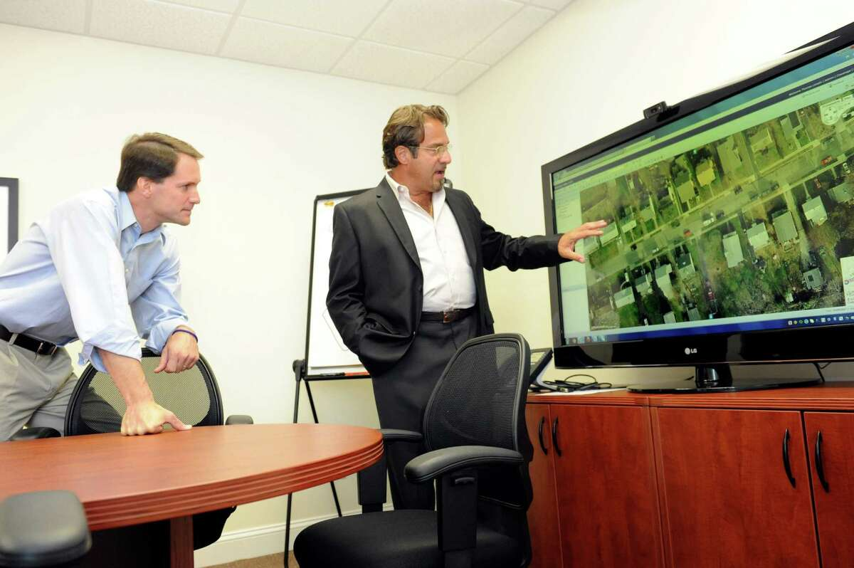 Tom Laredo, right, Renewable Resources director of sales and management, speaks with U.S. Rep Jim Himes about using pictometry to find the right place for a solar pannel. U.S. Rep Jim Himes visits Renewable Resources (Energy Solutions) Inc., in Stamford Tuesday, Aug. 7, 2012.