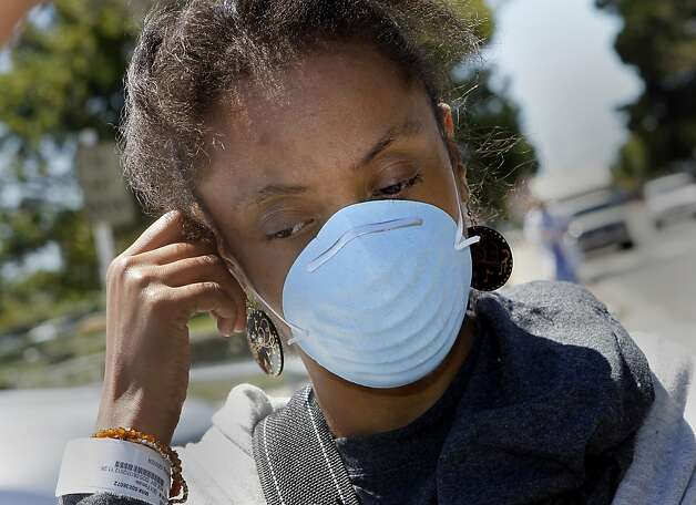 Mischa Adkins adjusts her breathing mask a day after she was exposed to smoke from the blaze. Adkins went with her boyfriend to Doctors Medical Center. The 32-year-old said she already has lupus and kidney problems. Photo: Brant Ward, The Chronicle