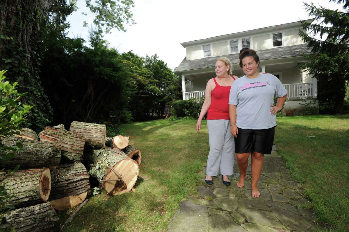 Barbara Cooper, left, and her daughter Elizabeth, inspect cut tree limbs in front of their Grimes Road home in Old Greenwich, Tuesday afternoon, Aug. 7, 2012. Cooper said tree limbs knocked down during the storm that hit Greenwich on Sunday fell on the power lines, causing a loss of electricity to their home for nearly two days.