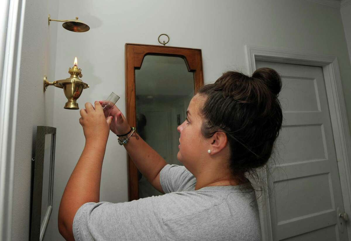 Elizabeth Cooper lights an oil lamp in the hallway of her Grimes Road home in Old Greenwich Tuesday afternoon, Aug. 7, 2012. Cooper's mother, Barbara, said a tree knocked down the power lines to their house during the storm that hit Greenwich on Sunday, and they were without power for nearly two days.