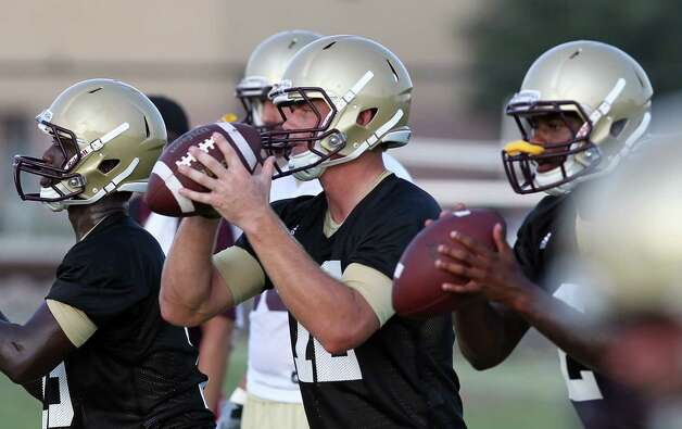 Texas State University quarterback Tyler Arndt (center) works on drills during football practice in San Marcos on Tuesday, August 7, 2012. Photo: Kin Man Hui, San Antonio Express-News / ©2012 San Antonio Express-News