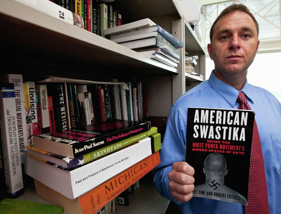 Pete Simi holds his book