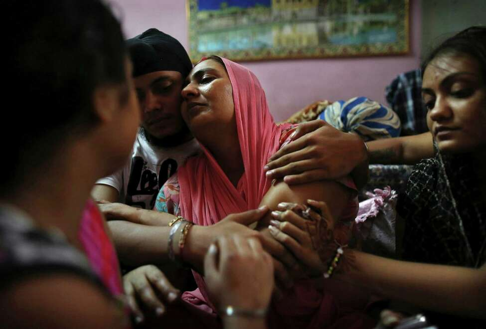 Indian Surinder Kaur, center, the wife of Seeta Singh who was killed in the shooting attack at a Sikh temple in Wisconsin, is comforted by her son Armeet and daughter Sarabjit, right, at the family home in New Delhi, India, Tuesday, Aug. 7, 2012. Seeta Singh was killed alongside his brother Ranjeet Singh who he had recently joined in the United States during the attack on Sunday. (AP Photo/Kevin Frayer)