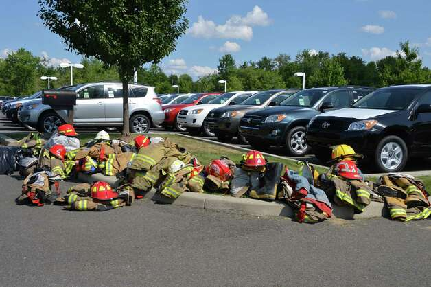 Firefighters' turnout gear stack next to new Toyotas at a staging area for a chemical fire at TCI, a transformer recycling company in Ghent at Kinderhook Toyota Thursday Aug. 2, 2012,   (John Carl D'Annibale/ Times Union) Photo: John Carl D'Annibale