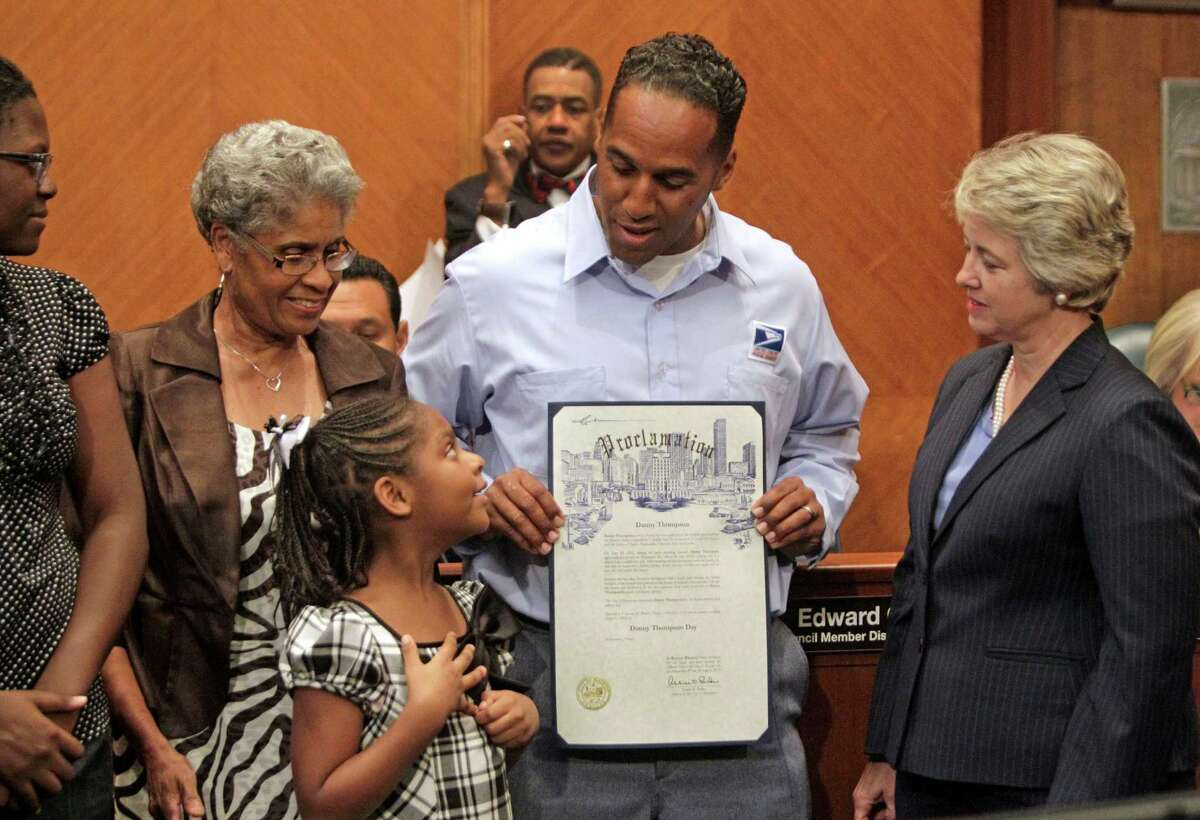 Chinyere Thompson, 15, her sister, Asia Thompson, 7, their grandmother, Dedriel Thompson, their dad, U.S. Postal Service employee Danny Thompson and City of Houston Mayor Annise Parker, right, line up to pose for photos after a proclamation declaring