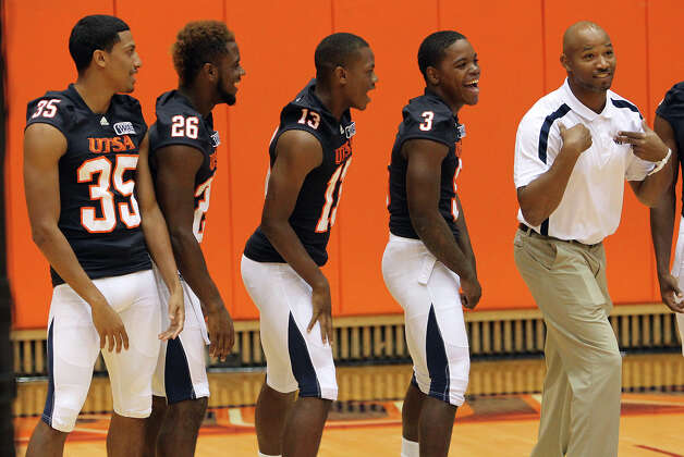 UTSA football assistant coach Nathaniel Jones (right) join in hamming it up for the cameras with players Xavier Archangel (35), Ja'Len James (26), Tre Rosser (13) and Alondre Thorn (03) duirng football media day at the Convocation Center on Tuesday, August 7, 2012. Photo: Kin Man Hui, San Antonio Express-News / ©2012 San Antonio Express-News