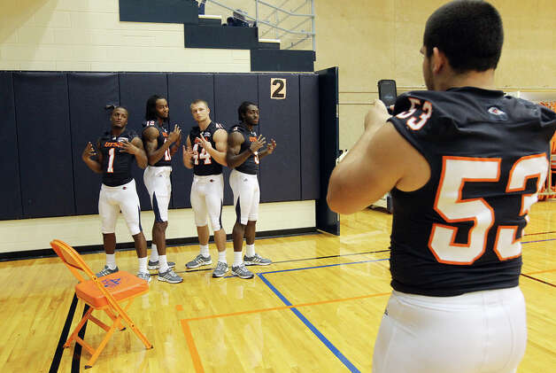 UTSA football players Kam Jones (01), Earon Holmes (12), Steven Kurfehs (44) and Marcellus Mack (09) pose for a picture from teammate Brandon Reeves (53) during football media day at the Convocation Center on Tuesday, August 7, 2012. Photo: Kin Man Hui, San Antonio Express-News / ©2012 San Antonio Express-News