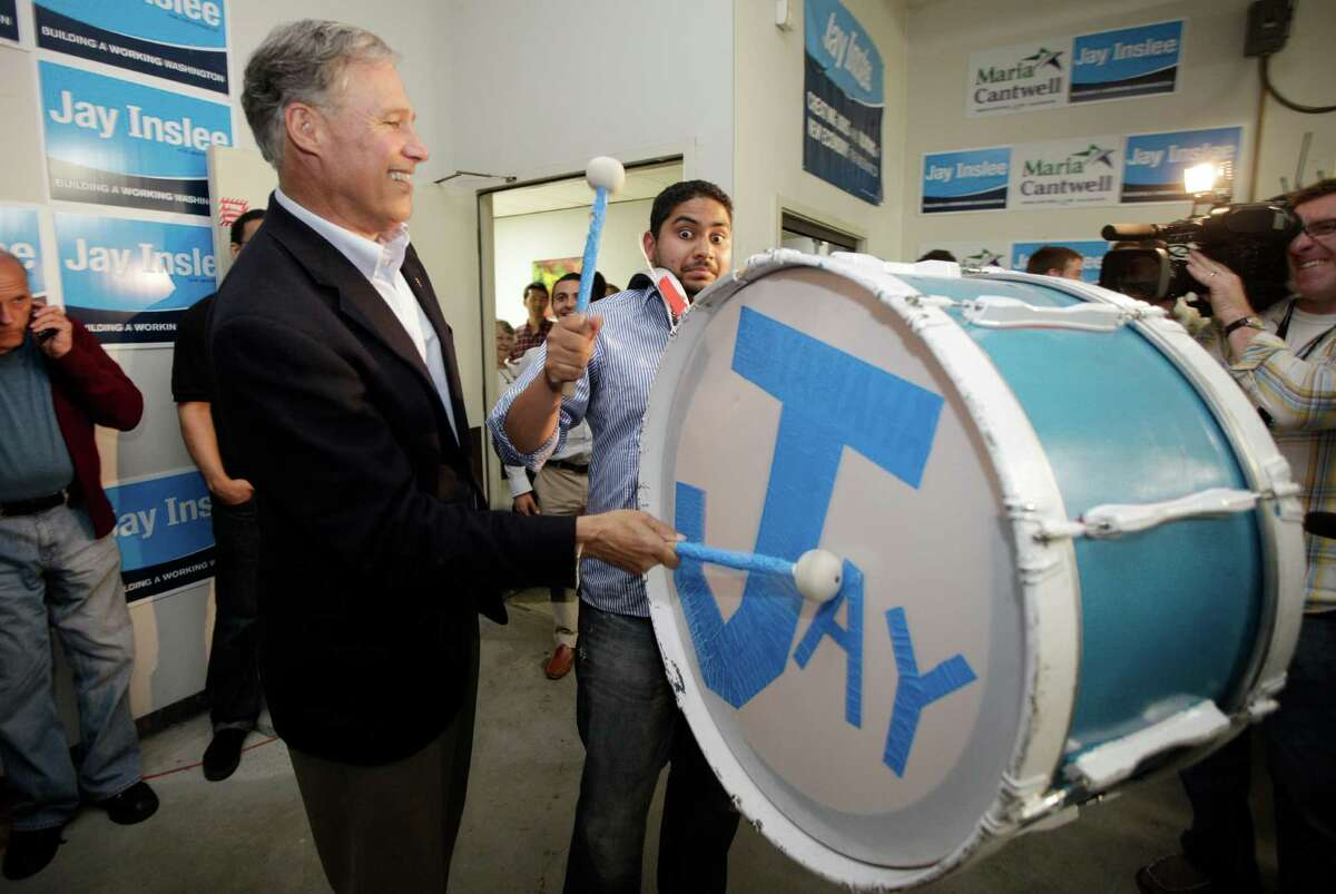 Jay Inslee, left, the Democratic candidate for Washington state governor, bangs on a drum held by campaign policy associate Richard Lazaro, right, as they celebrate early election returns, Tuesday, Aug. 7, 2012, on Washington's primary election day, at Inslee headquarters in Seattle.