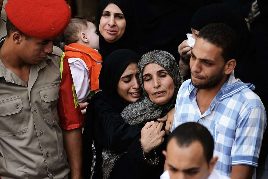 "Egyptian women and men mourn as Egyptian Army military policemen carry the coffin of one of the 16 soldiers killed during an attack on a border crossing post in Northern Sinai, during their funeral on August 7, 2012 in Cairo, Egypt. President Mohamed Morsi ordered security forces to take full control of the Sinai Peninsula and Egypt's army vowed to ""avenge"" the killings, in which 35 gunmen in Bedouin clothing opened fire on the troops before crossing into the Jewish state in an armoured vehicle, killing five on their side according to the Israelis. Photo: Gianluigi Guercia, AFP/Getty Images"