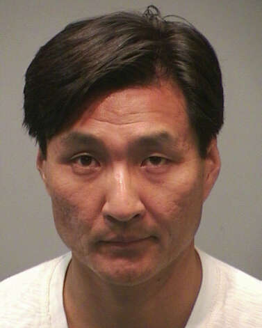 "Sung-Ho Hwang, 46, a New Haven, Conn. attorney, was arrested at a New Haven movie theater prior to a showing of ""The Dark Knight Rises"" after police said he was seen carrying a handgun in his waistband. Police said Hwang has a permit to carry a pistol, but didn't comply with their orders when they questioned him inside the theater. He was charged with breach of peace and interfering with an officer. Photo: Contributed"