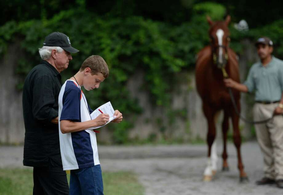 J.J. Pletcher. left father of famed trainer Todd Pletcher gives his grandson Peyton Pletcher some training as they look over some of the yearlings for sale at the Fasig Tipton Sales grounds in Saratoga Springs, N.Y. August 5, 2012.  Two nights of yearling sales start tomorrow evening in Saratoga. Photo: Skip Dickstein, TIMES UNION