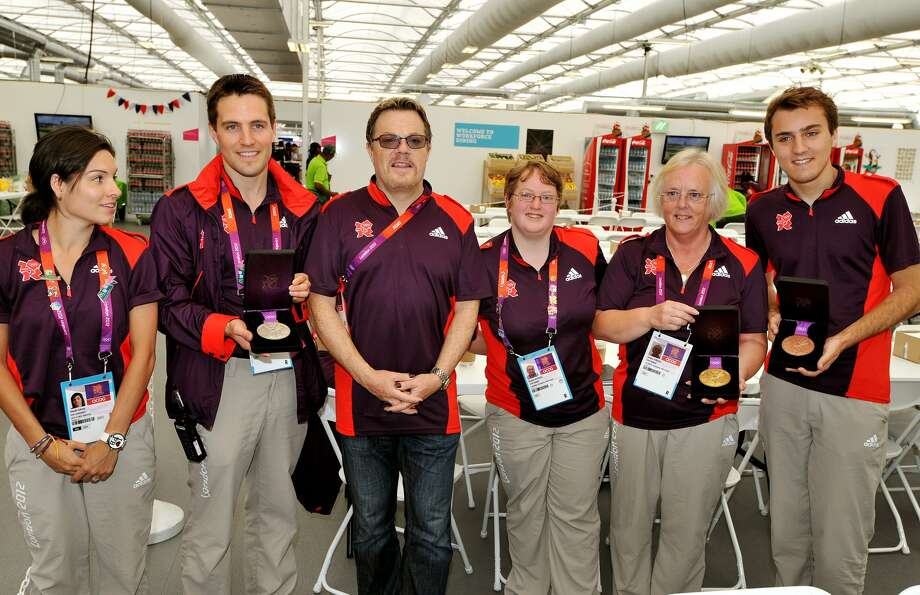 Comedian Eddie Izzard meets volunteer workers in the Athletes food hall as they hold Gold, Silver, and Bronze Medals. (Photo by John Stillwell - WPA Pool/Getty Images) (WPA Pool / Getty Images)