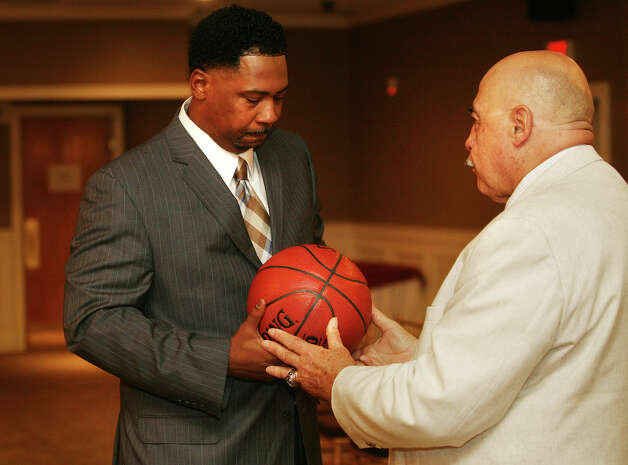 St. Joseph High School basketball coach Vito Montelli, right, passes the ball to his successor, Chris Watts, during a press conference at Vazzano's Four Seasons in Stratford on Wednesday, August 8, 2012. Watts is both former St. Joseph player and assistant coach. Photo: Brian A. Pounds / Connecticut Post