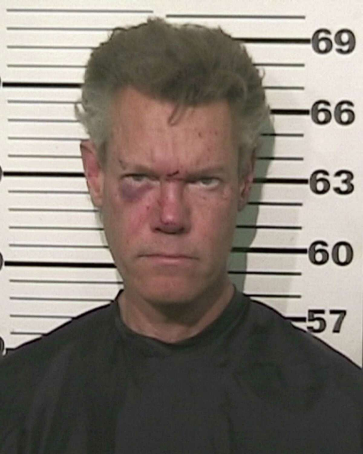Randy Travis Aside from this mug shot, nothing was funny about Randy Travis' August 2012 arrest on DWI charges after he was found naked on a road near his home in the North Texas town of Tioga. Two weeks later, he was accused of assault after brawling with his girlfriend's estranged husband in the parking lot of a Plano church. Witnesses to the fight told TMZ that the county legend appeared