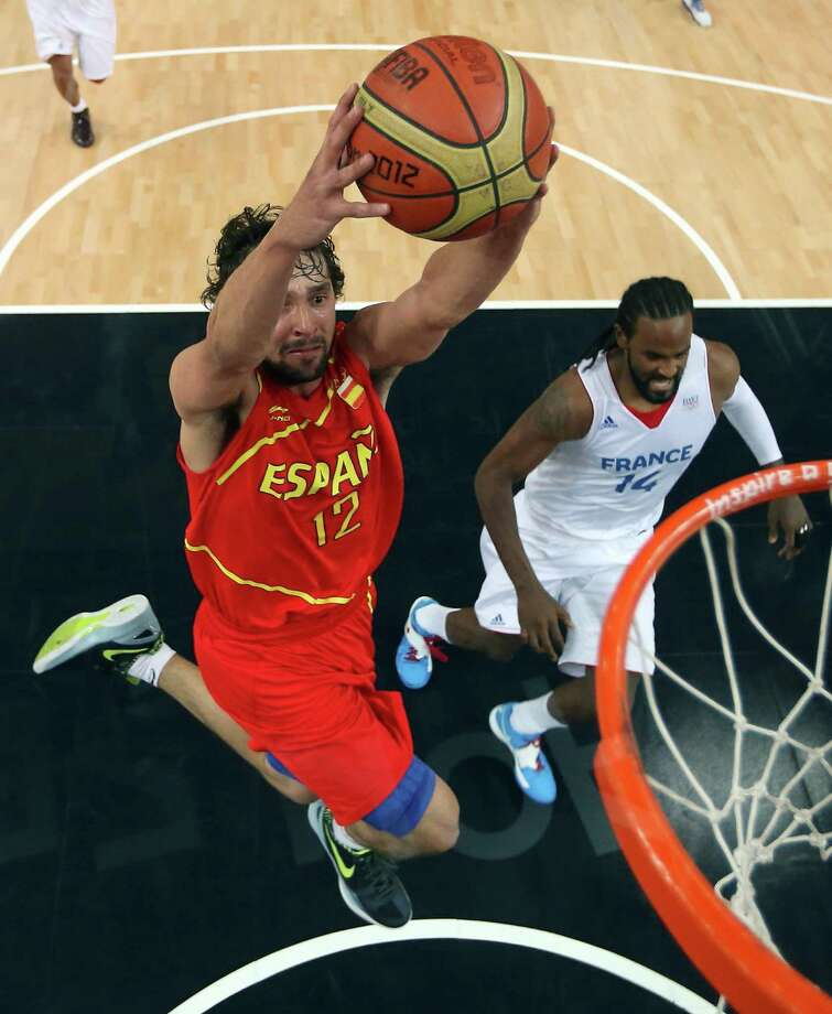 LONDON, ENGLAND - AUGUST 08: (EDITORS NOTE: A polarizing filter was used for this image.) Sergio Llull #12 of Spain goes up for a dunk in front fo Ronny Turiaf #14 of France in the fourth quarter during the Men's Basketball quaterfinal game on Day 12 of the London 2012 Olympic Games at North Greenwich Arena on August 8, 2012 in London, England. Photo: Christian Petersen, Getty Images / 2012 Getty Images