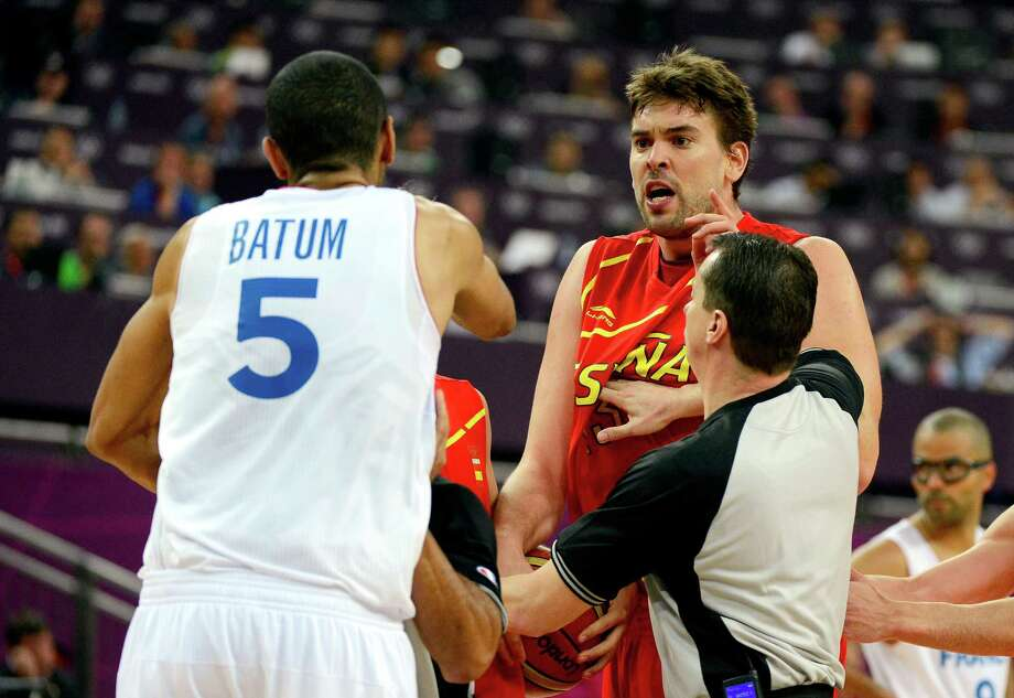 LONDON, ENGLAND - AUGUST 08:  Marc Gasol #13 of Spain is held back by a referee as he runs towards Nicolas Batum #5 of France after Batum fouled Juan-Carlos Navarro #7 late in the fourth quarter during the Men's Basketball quaterfinal game on Day 12 of the London 2012 Olympic Games at North Greenwich Arena on August 8, 2012 in London, England. Photo: Ronald Martinez, Getty Images / 2012 Getty Images