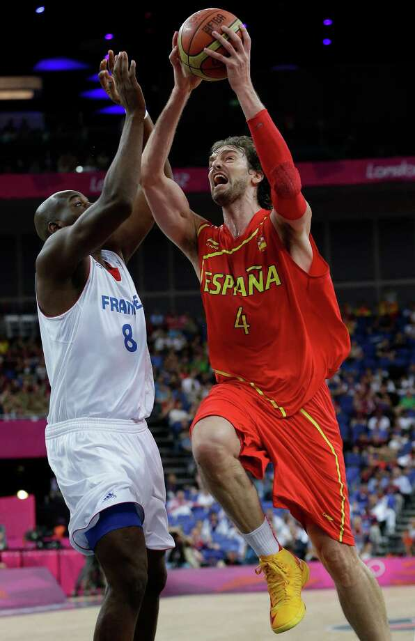 Spain's Pau Gasol (4) drives to the basket as France's Ali Traore (8) defends during a quarterfinal men's basketball game at the 2012 Summer Olympics, Wednesday, Aug. 8, 2012, in London. (AP Photo/Eric Gay) Photo: Eric Gay, Associated Press / AP
