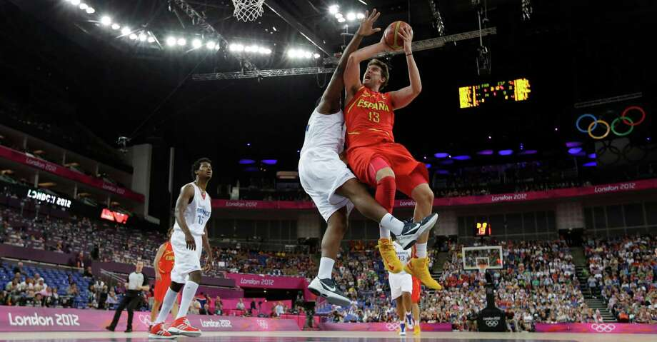 Spain's Marc Gasol (13) is defended by France's Kevin Seraphin, left, as he tries to score during a quarterfinal men's basketball game at the 2012 Summer Olympics, Wednesday, Aug. 8, 2012, in London. (AP Photo/Eric Gay) Photo: Eric Gay, Associated Press / AP