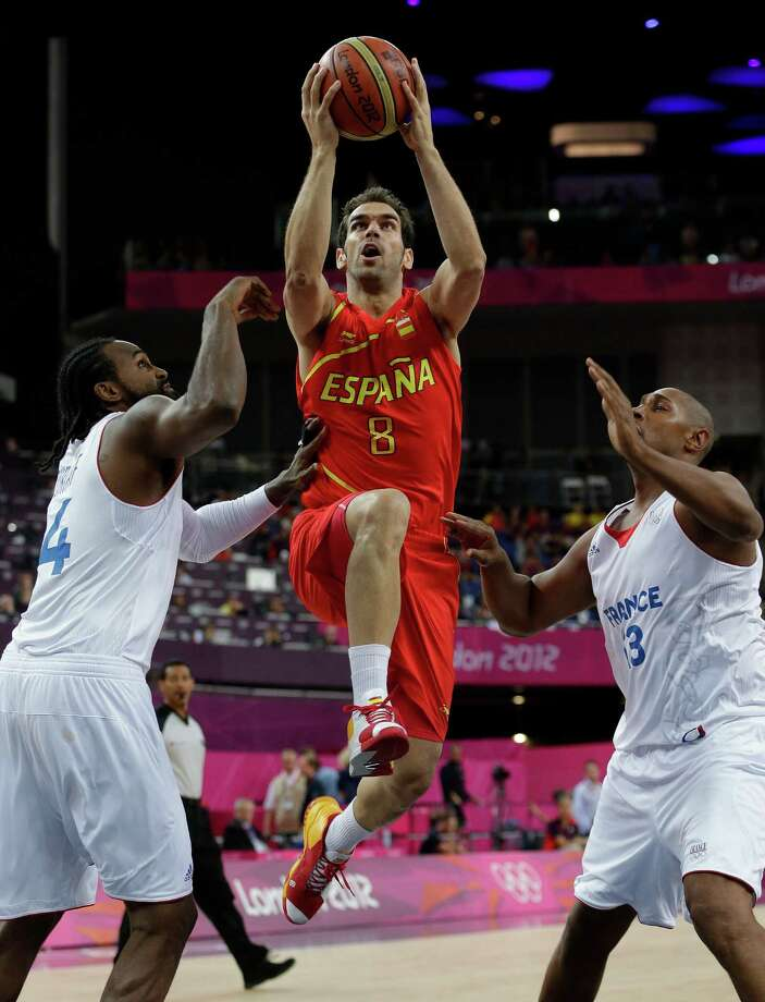 Spain's Jose Calderon (8) drives between France defenders Ronny Turiaf, left. and  Boris Diaw, right, during a quarterfinal men's basketball game at the 2012 Summer Olympics, Wednesday, Aug. 8, 2012, in London. (AP Photo/Eric Gay) Photo: Eric Gay, Associated Press / AP