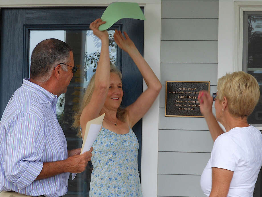 "Kathy Ross unveils a plaque recognizing the new Longshore Golf Course halfway house as ""Cliff's Place,"" in tribute to her late husband Cliff Ross, during dedication ceremonies Tuesday. Photo: Mike Lauterborn / Westport News contributed"