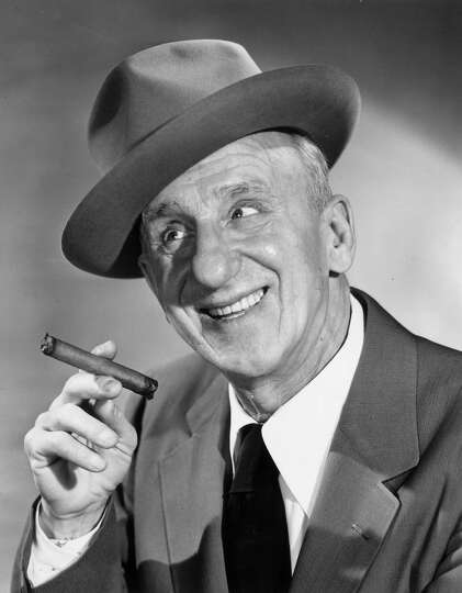 circa 1955: American comedian Jimmy Durante (1893 - 1980) smiling and holding a cigar. He wears a ha