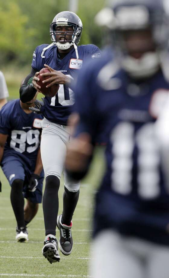Seattle Seahawks' Terrell Owens runs with a football that was tossed to him during stretching drills at the start of NFL football training camp, Wednesday, Aug. 8, 2012, in Renton, Wash. (Ted S. Warren / Associated Press)