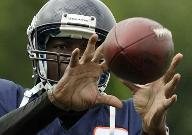 ALTERNATE CROP - Seattle Seahawks' Terrell Owens catches a football during stretching drills at the start of NFL football training camp, Wednesday, Aug. 8, 2012, in Renton, Wash. (Ted S. Warren / Associated Press)