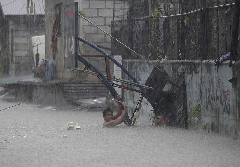 Amid driving rain, a Filipino clings to the pole of a basketball backboard as he tries to cross a flooded area in Quezon City, north of Manila. Photo: Aaron Favila, Associated Press