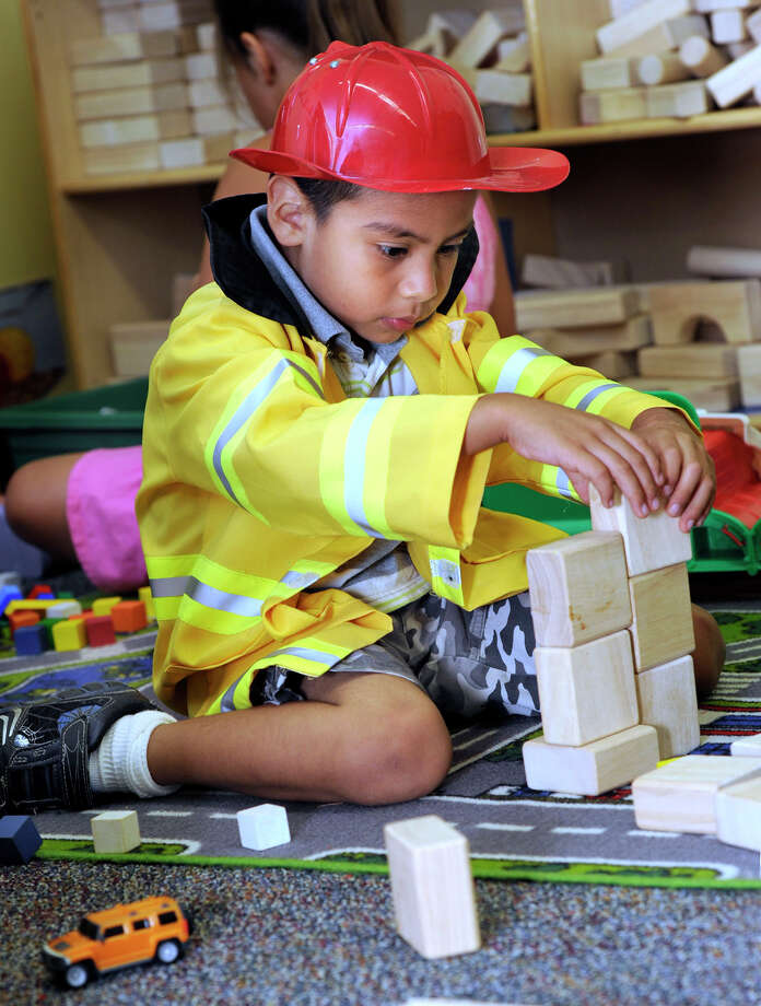 Luis Giron, 5, wears a fireman's suit and plays with blocks during a freeplay time period at Kindergarten Boot Camp Wednesday morning, Aug. 8, 2012. The camp is run by the Danbury Family Literacy Center. Photo: Carol Kaliff / The News-Times