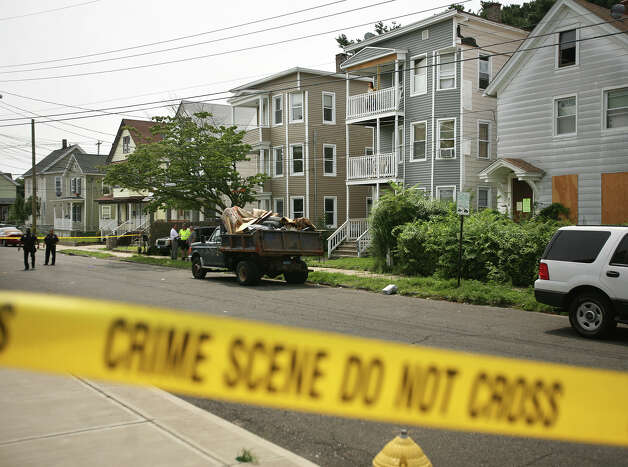 Police investigate the scene of a shooting at 505 Park Street in Bridgeport, the three family home second from right, on Wednesday, August 8, 2012. Photo: Brian A. Pounds / Connecticut Post