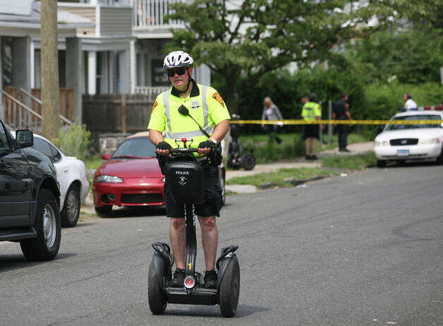 A police office on a segway patrols the street outside the scene of a shooting at 505 Park Street in Bridgeport on Wednesday, August 8, 2012. Photo: Brian A. Pounds / Connecticut Post