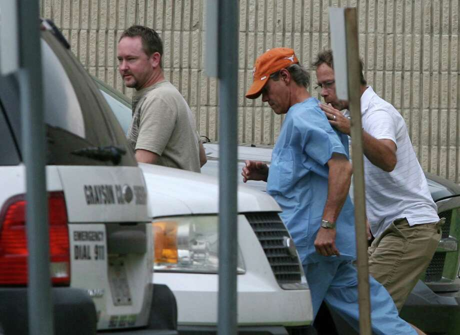 Randy Travis, center wearing cap, exits the Grayson County jail with two unknown persons Wednesday Aug. 8, 2012, in Sherman, Texas, after being arraigned on charges of driving while intoxicated and retaliation. (AP Photo/The Herald Democrat, Chris Jennings) TV OUT; MAGS OUT; TV AND MAGAZINE CALL FOR RATES TERMS;MANDATORY CREDIT Photo: Chris Jennings, Associated Press / The Herald Democrat