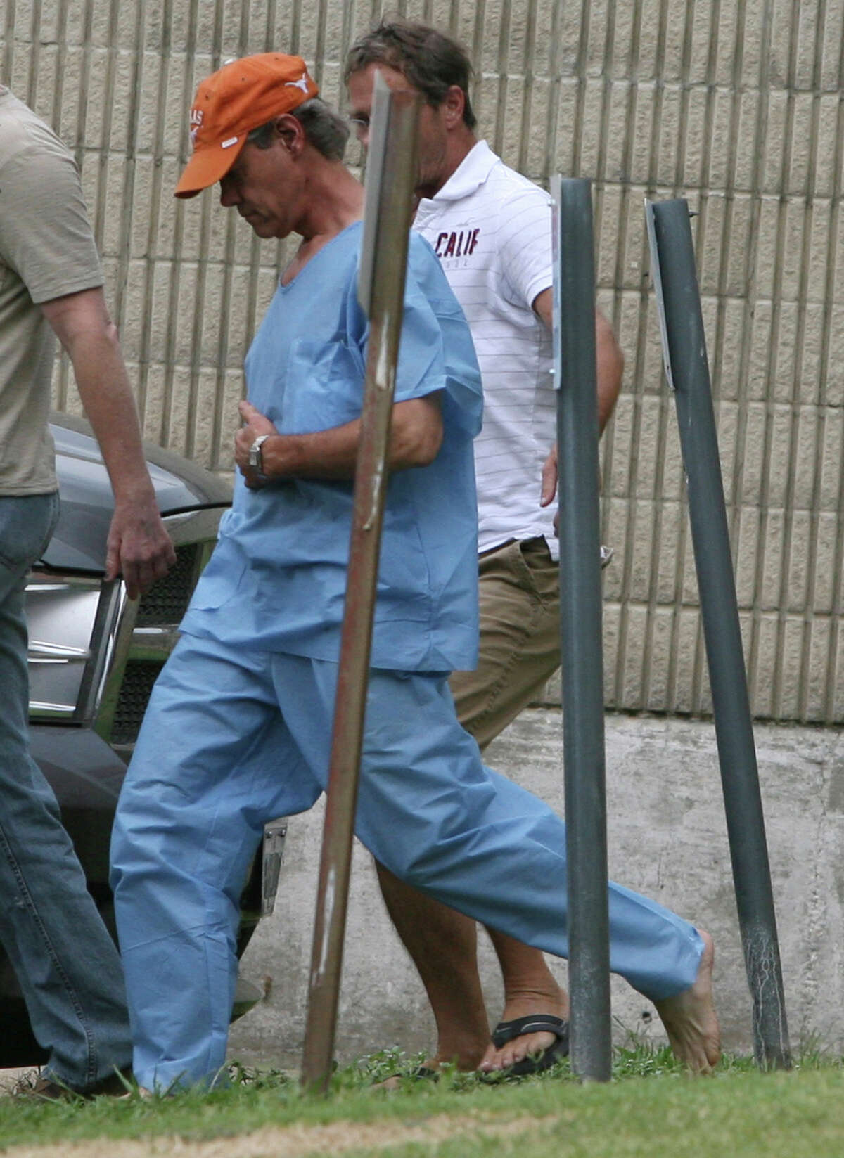 Randy Travis, center, wearing cap, exits the Grayson County jail with two unknown persons Wednesday Aug. 8, 2012, in Sherman, Texas, after being arraigned on charges of driving while intoxicated and retaliation. (AP Photo/The Herald Democrat, Chris Jennings) TV OUT; MAGS OUT; TV AND MAGAZINE CALL FOR RATES TERMS;MANDATORY CREDIT