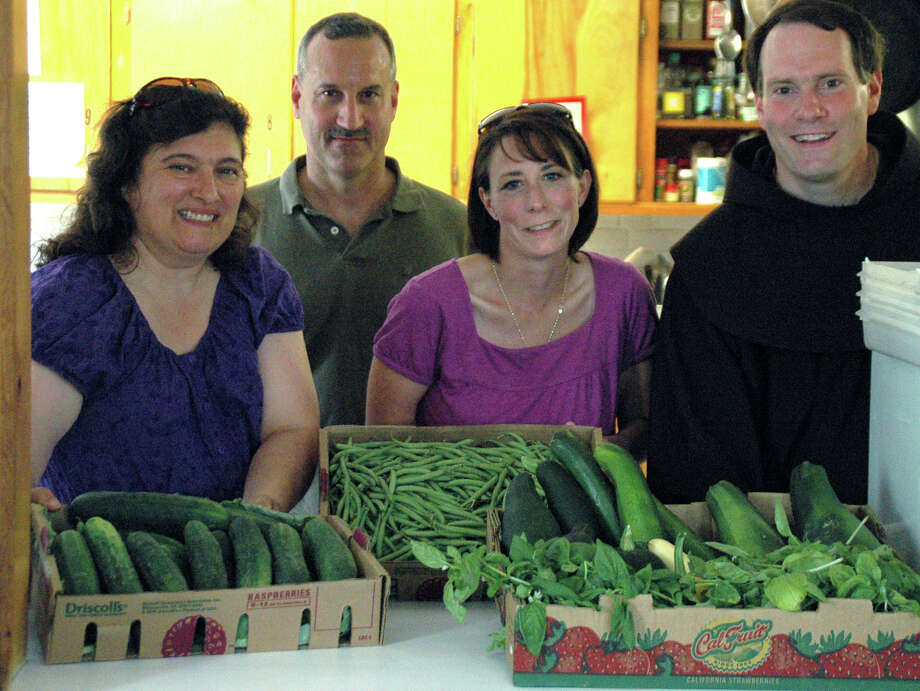 Happily accepting the donation of fresh produce at the Loaves & Fishes Hospitality House in New Milford is Loaves president Lisa Martin, left. Representing St. Francis Xavier Church are parish council president Kim Ginn, center, Father Larry Perent, Office of Friars Minor, pastor of St. Francis Xavier Church, and, in back, Stephen Fugardi, garden ministry coordinator. August 2012  Courtesy of  St. Francis Xavier Church Photo: Contributed Photo