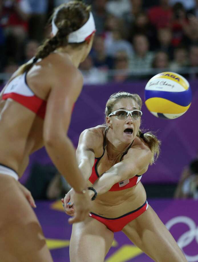 United States' Kerri Walsh Jennings, right, lsets a ball for Misty May-Treanor, left, during the women's gold medal beach volleyball match against the other US team at the 2012 Summer Olympics, Wednesday, Aug. 8, 2012, in London. Photo: Ap