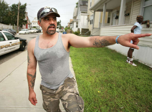 Park Street resident Reynaldo Santiago points toward the scene of a shooting at 505 Park Street in Bridgeport on Wednesday, August 8, 2012. Photo: Brian A. Pounds / Connecticut Post