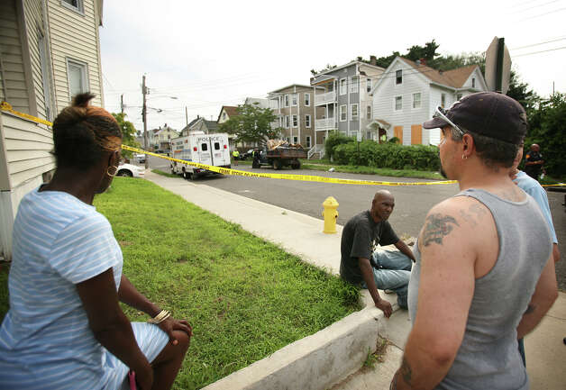 Neighborhood residents wait behind police tape at the scene of a shooting at 505 Park Street in Bridgeport on Wednesday, August 8, 2012. Photo: Brian A. Pounds / Connecticut Post