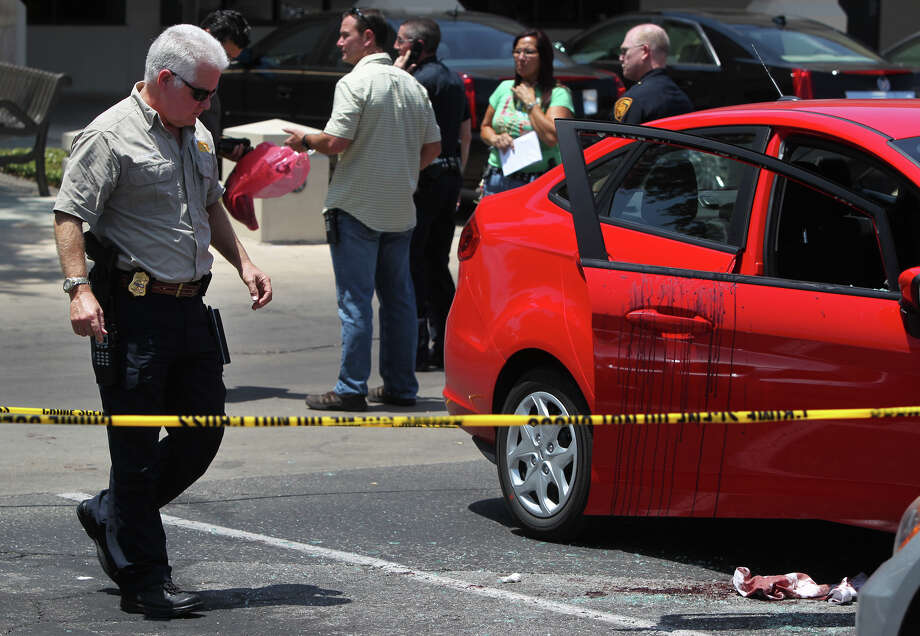 Police work at the scene of a stabbing that took place Wednesday August 8, 2012 in a shopping center paking lot on Basse road near the intersection of Nacogdoches. According San Antonio Police Sergeant Daniel Alonzo of the Robbery Task Force, a jewelry wholesaler visited a jewelry store, got some lunch and worked on his laptop computer. The man returned to his car, Alonzo said, when two males approached the car on each side and attacked the man. One of the robbers repeatedly stabbed the victim and the two robbers fled the scene in a black Chevy Impala with the victim's backpack. The victim is in critical condition at University Hospital and the suspects are currently at large and did not manage to steal any of the jewelry. Photo: John Davenport, San Antonio Express-News / John Davenport/©San Antonio Exp