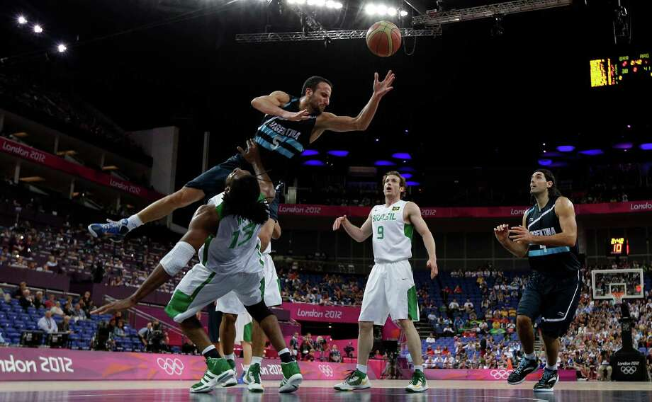 Argentina's Manu Ginobili (5) crashes into Brazil's Nene Hilario (13) during a quarterfinal men's basketball game at the 2012 Summer Olympics, Wednesday, Aug. 8, 2012, in London. (AP Photo/Eric Gay) Photo: Eric Gay, Associated Press / AP