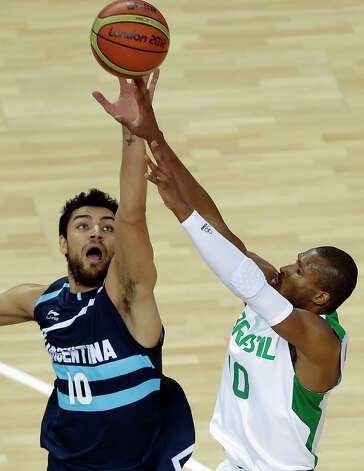 Argentina's Carlos Delfino, left, and Brazil's Leandrinho Barbosa, right, jump for a rebound during a men's basketball quarterfinal game at the 2012 Summer Olympics, Wednesday, Aug. 8, 2012, in London. (AP Photo/Victor R. Caivano) Photo: Victor R. Caivano, Associated Press / AP