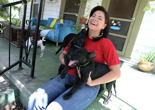 Lori Rodriguez, founder of Westside Dog Initiative, poses with two of her rescued dogs on Saturday, August 4, 2012. Rodriguez started in 2011 to rescue dogs to help decrease the stray animal population in her community. She also wanted to help educate residents about responsible pet ownership that involves spaying and neutering their pets. The initiative has been involved in community meetings to promote low-cost spaying and neutering programs. Though the initiative has a small network of animal foster homes, Rodriguez believes the efforts of the initiative is good for the community and for the lives of pets in San Antonio. Photo: Kin Man Hui, SAN ANTONIO EXPRESS-NEWS / ©2012 San Antonio Express-News