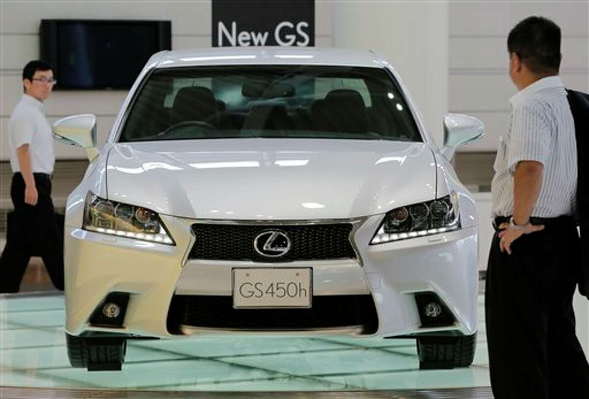 Visitors look at Toyota's Lexus GS 450h displayed at its showroom in Tokyo Friday, Aug. 3, 2012. Toyota Motor Corp. raised its sales target for this year to 9.76 million vehicles and reported a strong recovery in quarterly profit Friday, underlining its bounce back from a disaster plagued 2011. Toyota said April-June profit zoomed to 290.3 billion yen ($3.7 billion) from 1.1 billion yen the year before. (AP Photo/Itsuo Inouye)
