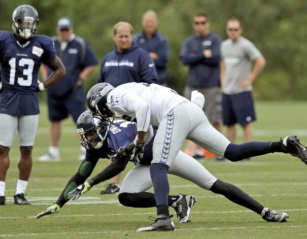 Seattle Seahawks' Terrell Owens, center left, is driven to the ground by cornerback Brandon Browner during NFL football training camp, Wednesday, Aug. 8, 2012, in Renton, Wash. (Ted S. Warren / Associated Press)